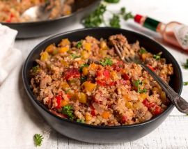 close up photo of cajun dirty rice in black bowl with fork