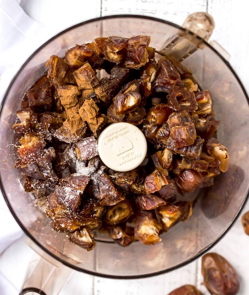 over head photo of food processor filled with dates, salt and cinnamon