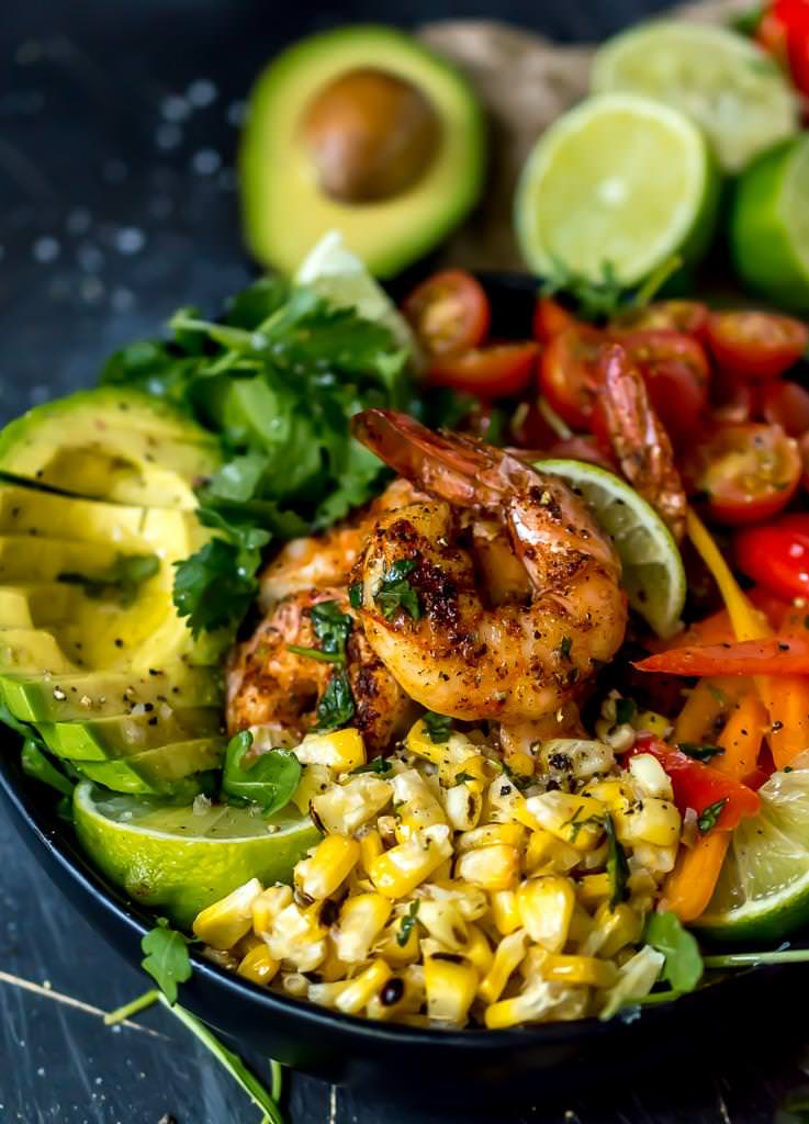 close up of spicy shrimp coated in seasoning with bright yellow roasted corn kernels in front and a sliced avocado on the side