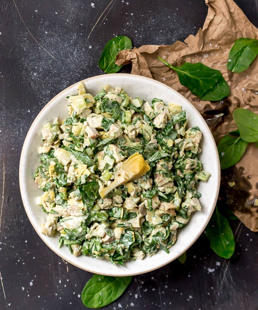 overhead photo of spinach artichoke chicken salad in white bowl. brown wrinkled paper and fresh spinach leaves on the side