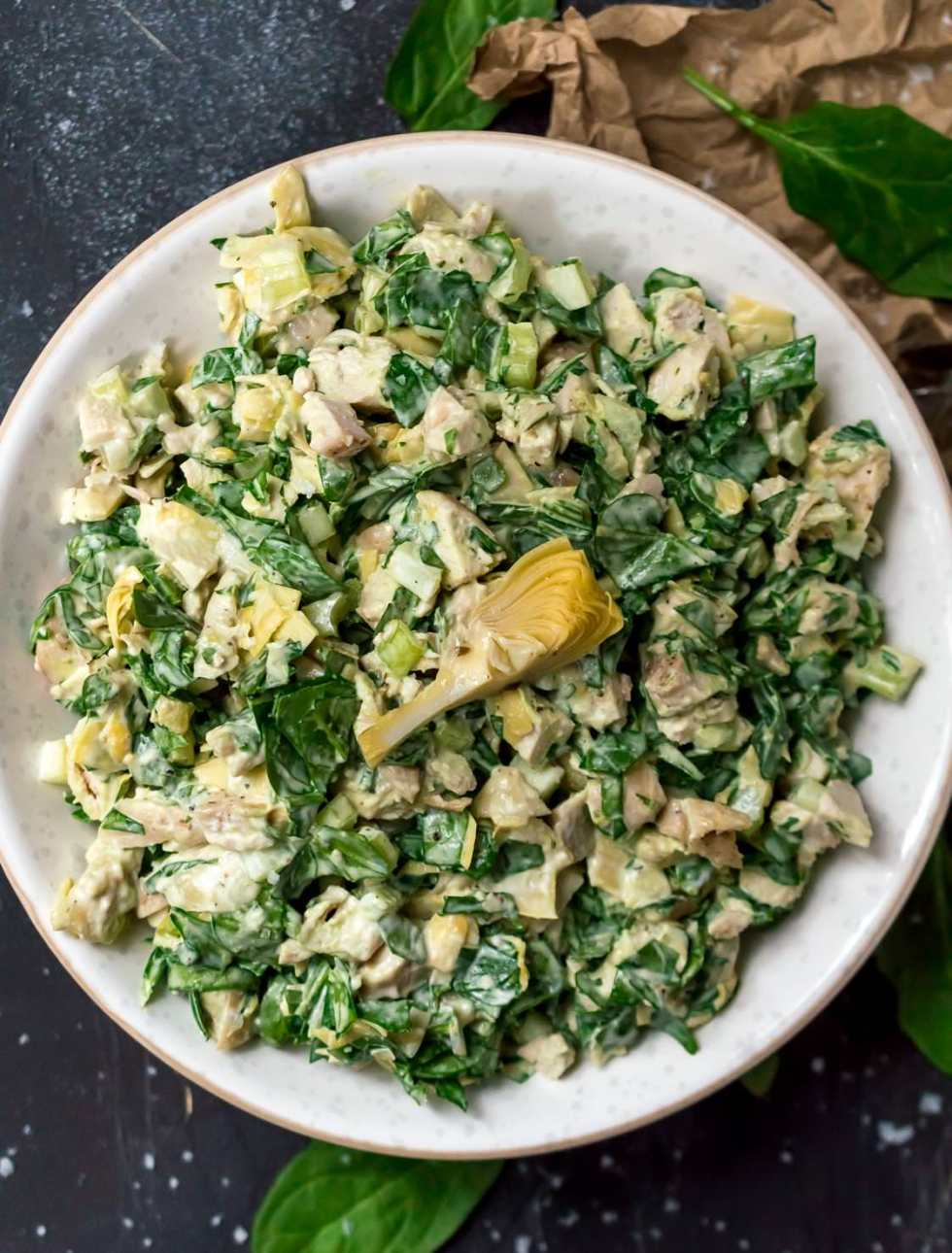 close up over head photo of green spinach artichoke chicken salad in white bowl