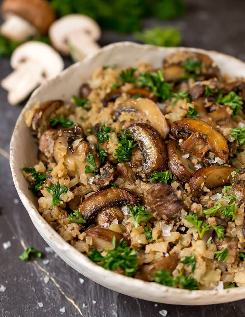 close up of cauliflower mushroom rice with brown mushrooms and green fresh parsley