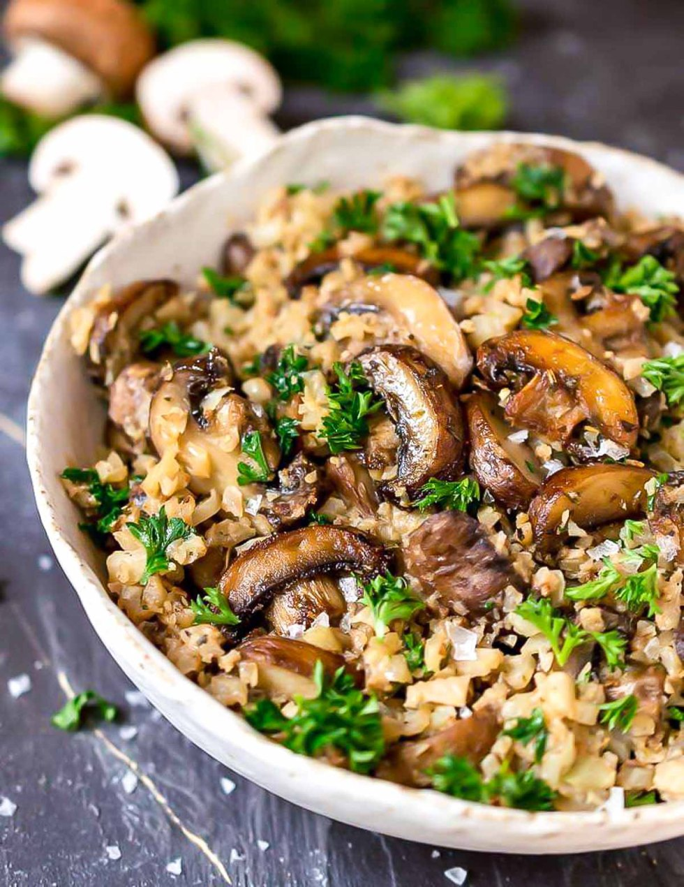 white bowl filled with golden mushrooms, cauliflower rice and parsley