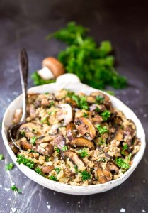 mushroom cauliflower rice in white bowl with spoon