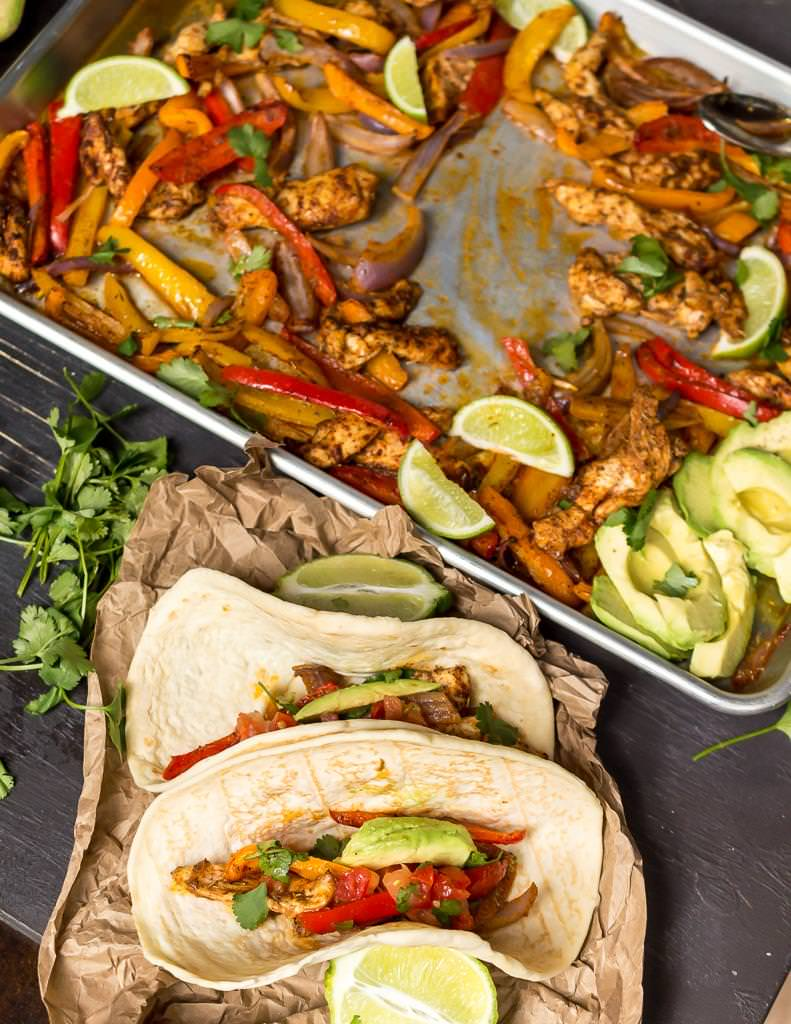 two assembled chicken fajitas with the sheet pan in the background