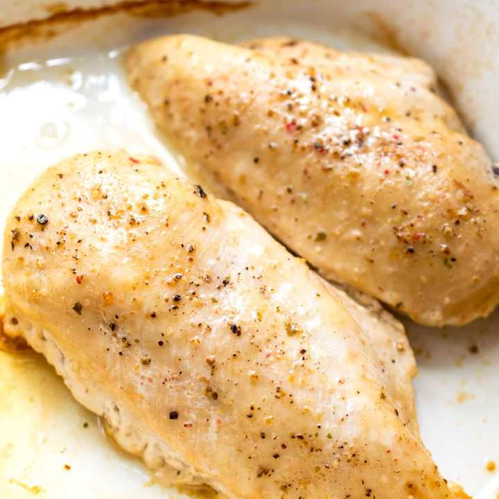 oven baked chicken breast topped with salt and pepper in white baking dish