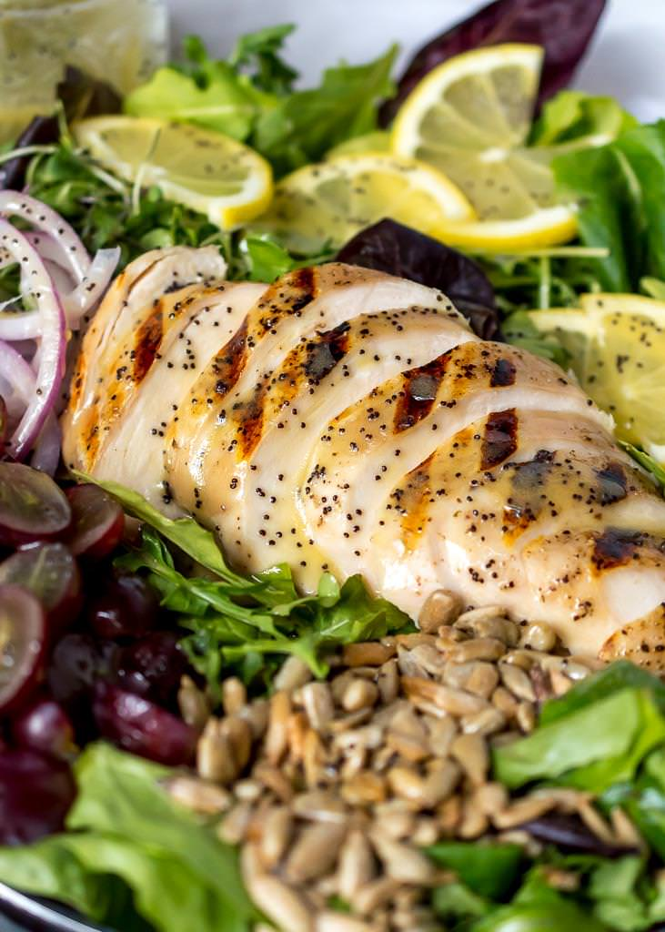 close up photo of grilled chicken on top of salad with sunflower seeds and red grapes, lemon poppy seed dressing on top