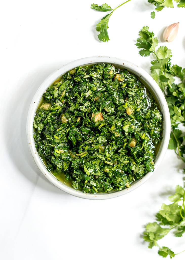 over head image of bright green roasted garlic cilantro chimichurri sauce with cilantro and garlic on the side