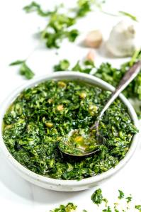 chimichurri in white bowl with silver spoon