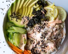 over head photo of sushi bowl filled with avocado, cucumber, carrots, lemon, crab and seaweed