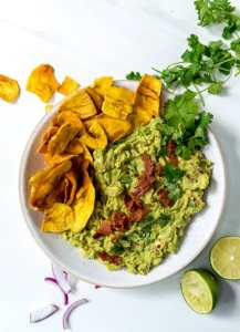 over head photo of bacon guac mixed together in a white bowl with plantain chips on the side