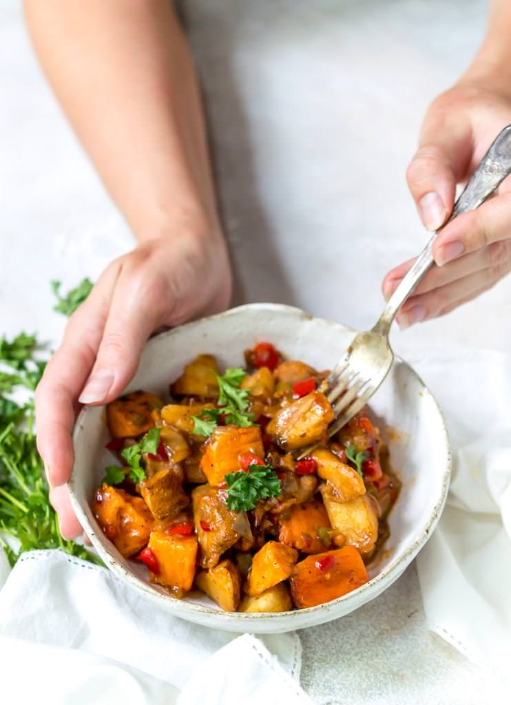 hand holding white bowl and fork scooping a bite of an easy weeknight dinner, chipotle chicken vegetable hash