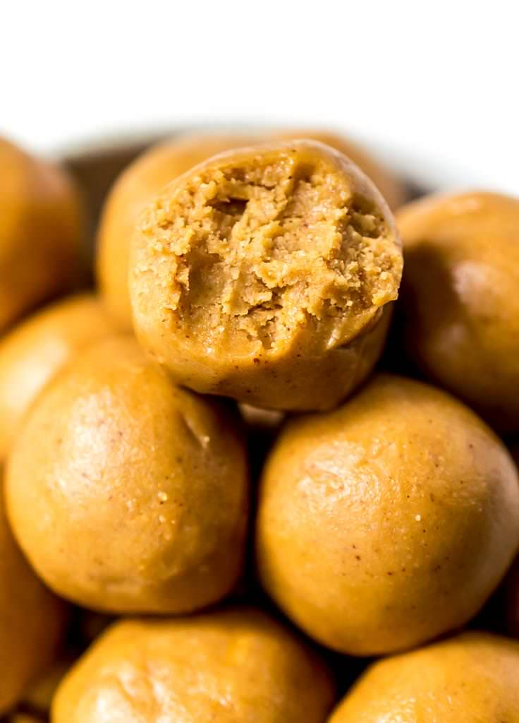 close up photo of peanut butter protein balls with a bite taken out of it