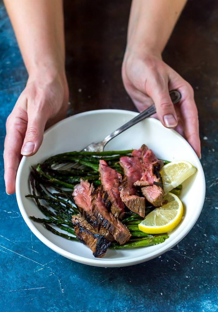 flank steak recipe over roasted asparagus with lemons in white bowl held by two hands