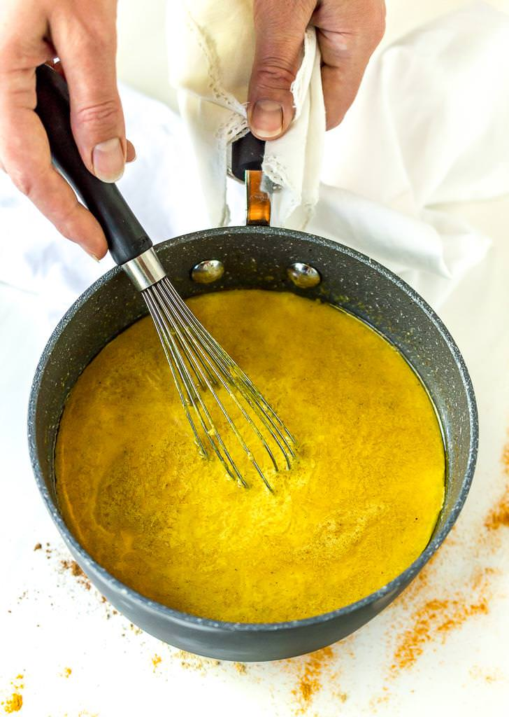 golden milk being prepared in small pot with whisk