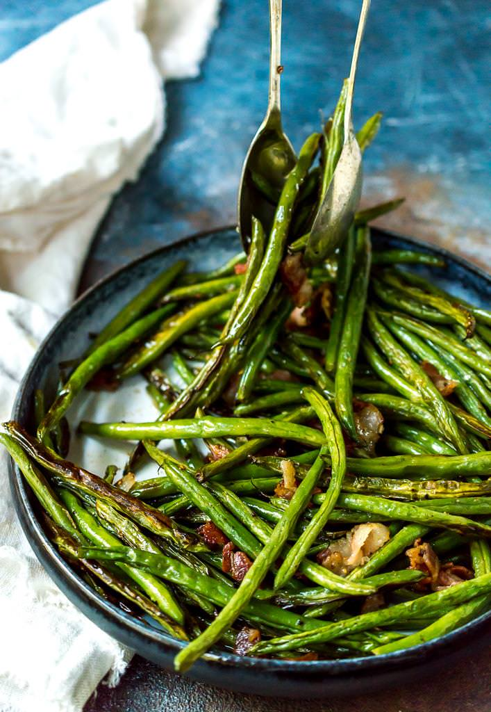 roasted green beans with bacon being served with utensils