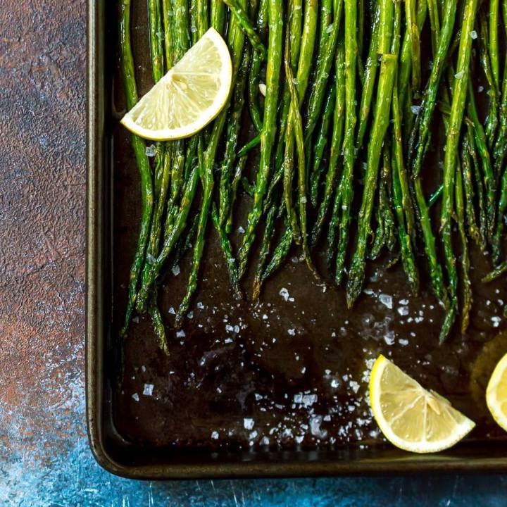 oven roasted asparagus recipe on baking sheet with lemon slices