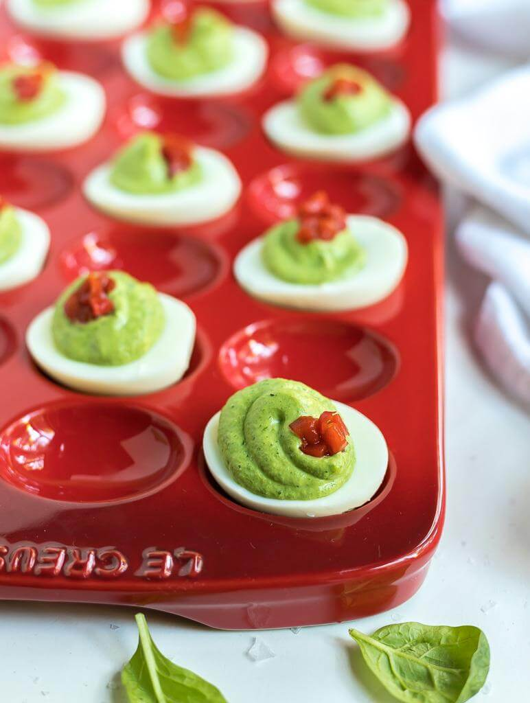 green and red deviled eggs in red serving platter