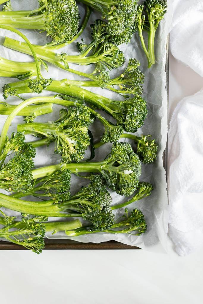 fresh raw broccolini on parchment paper for roasted broccolini recipe