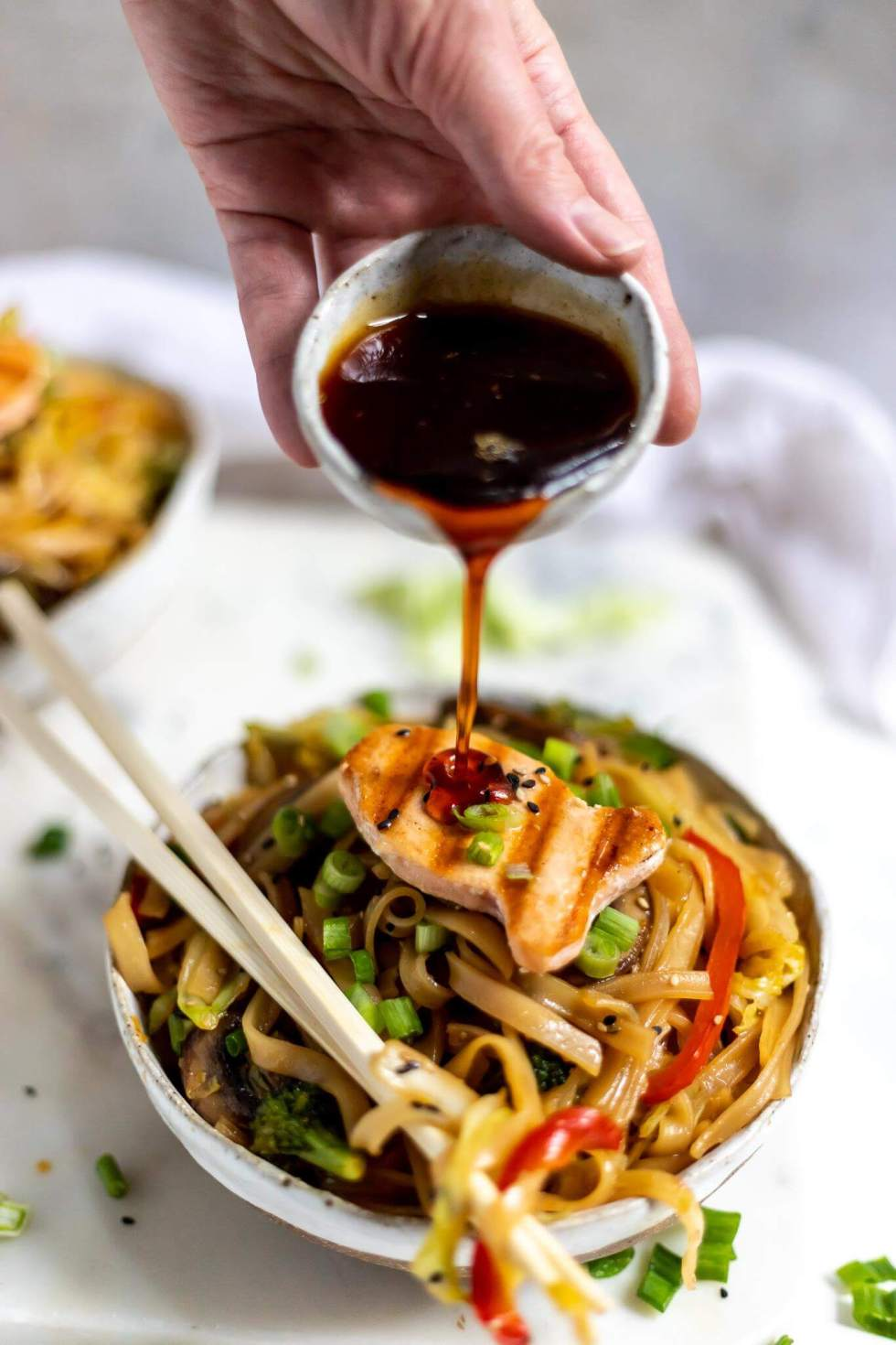 bowl of chinese noodles topped with salmon, sticky ginger soy sauce being poured over the top