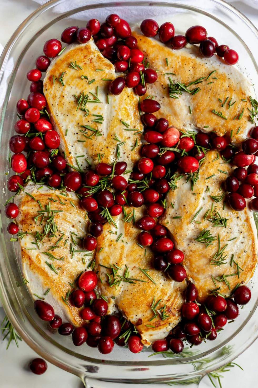 rosemary chicken breasts and fresh red cranberries in glass baking dish