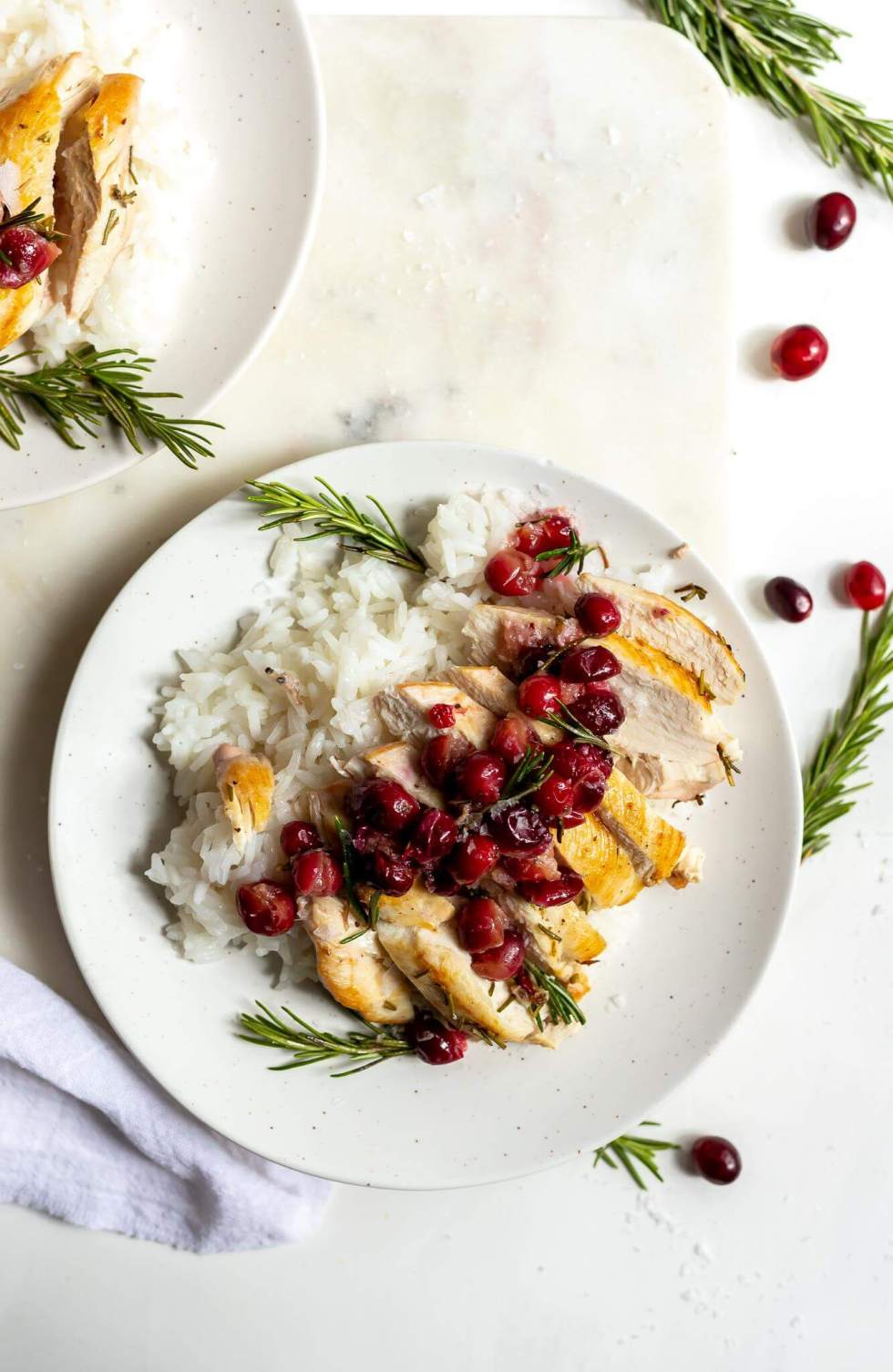 sliced rosemary chicken topped with cranberries served with white rice on a white plate