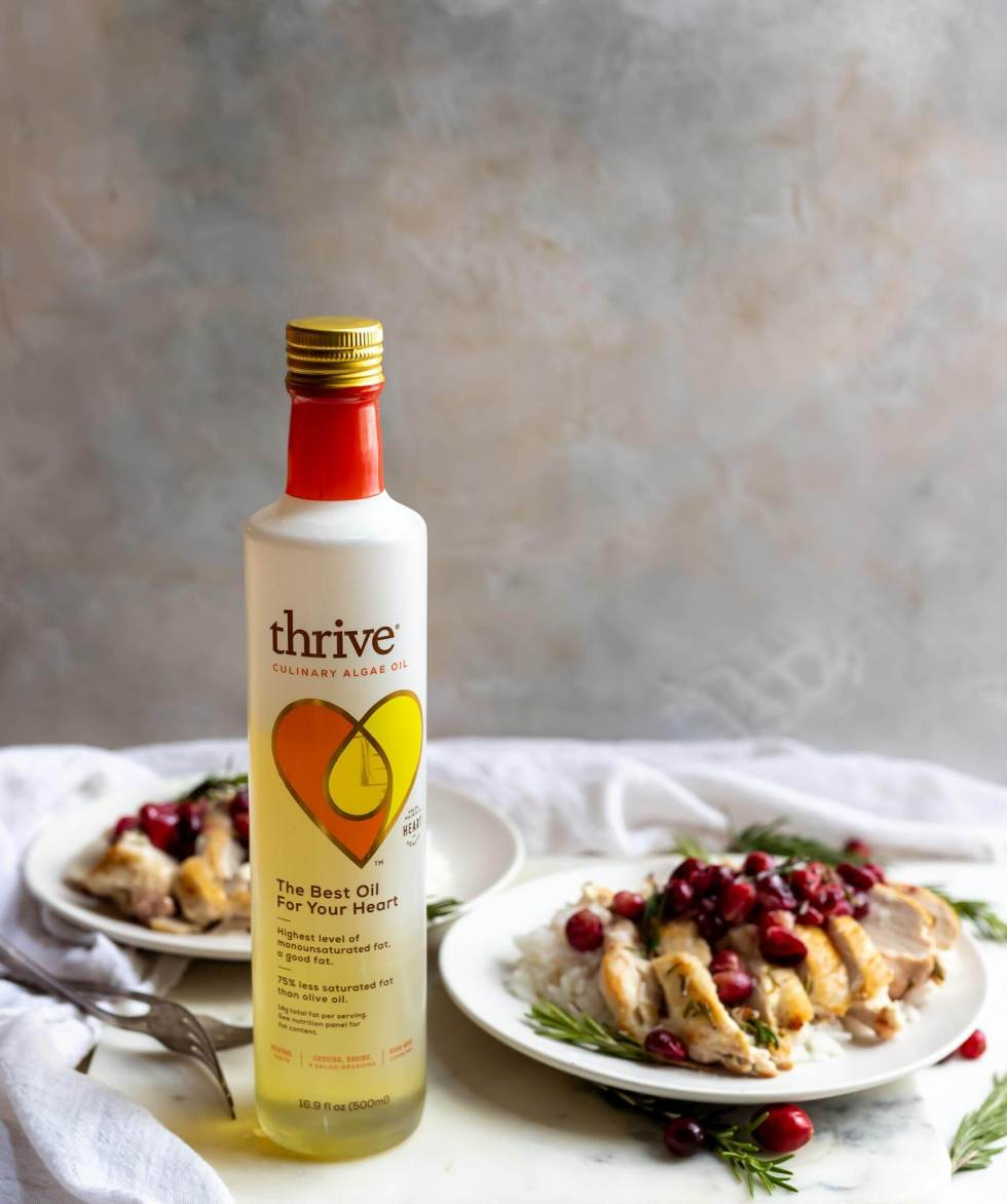 cranberry rosemary chicken served on white plates next to a bottle of thrive oil