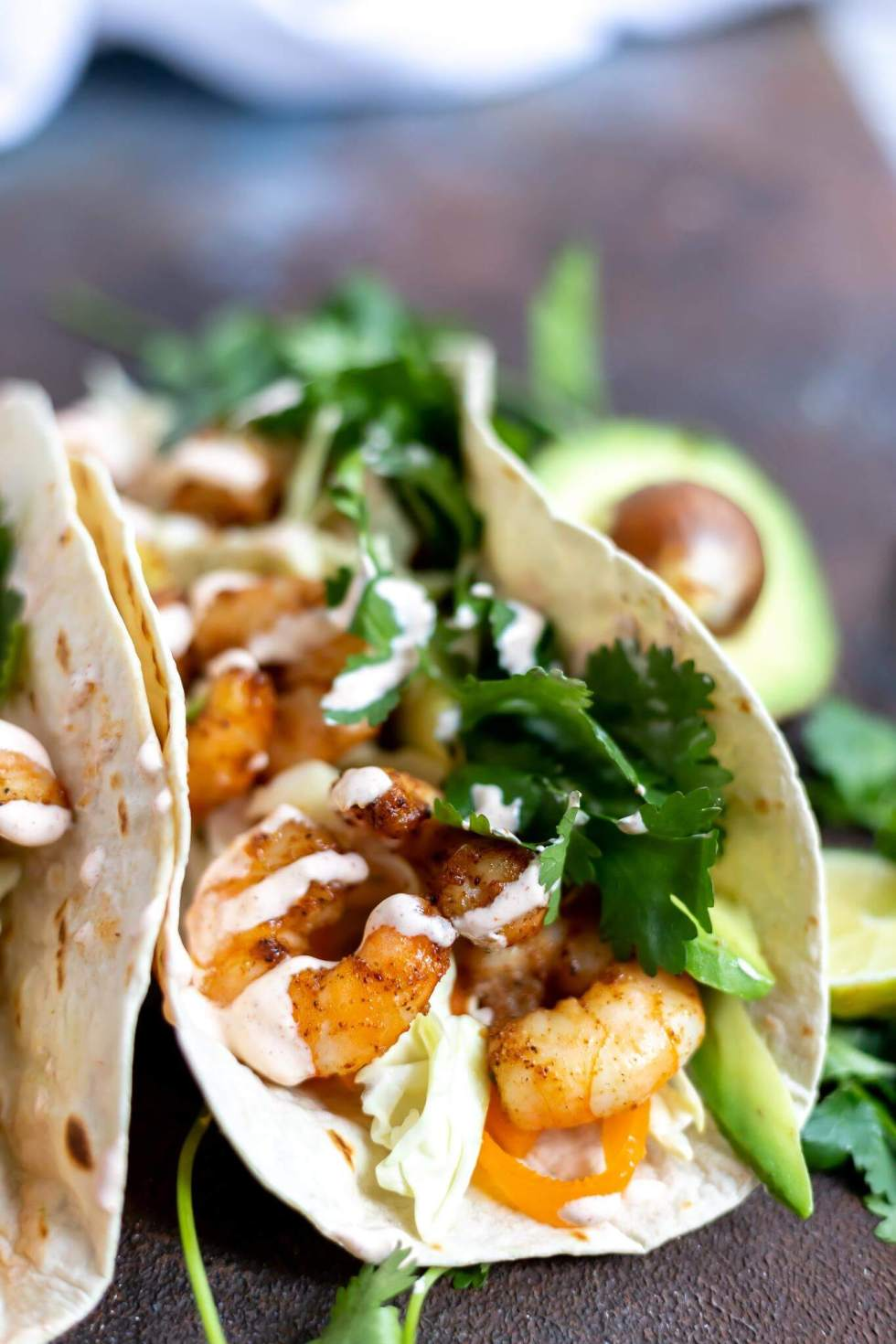 tortilla loaded with shrimp, cilantro, avocado, cabbage and a creamy sauce for shrimp tacos