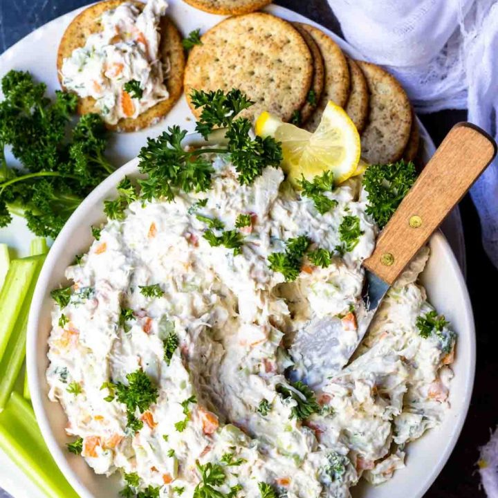 cold crab dip in white bowl with metal spreading knife