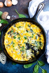 mushroom spinach frittata recipe in black cast iron pan with a slice removed