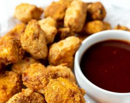 homemade air fryer chicken nuggets on a white plate with barbecue sauce on the side