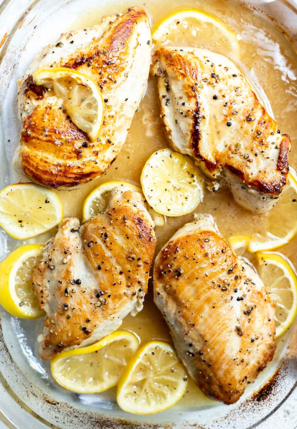 lemon pepper chicken in glass baking dish with lemon slices