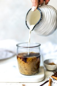 paleo vegan coffee creamer being poured into clear glass of coffee