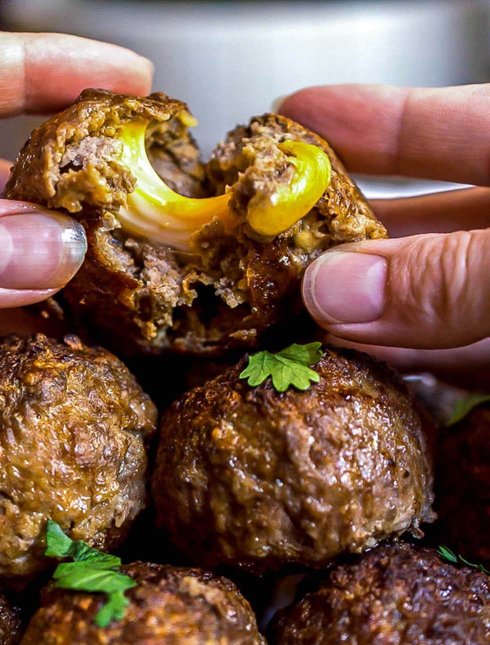 hands pulling apart a stuffed meatball with cheese oozing out