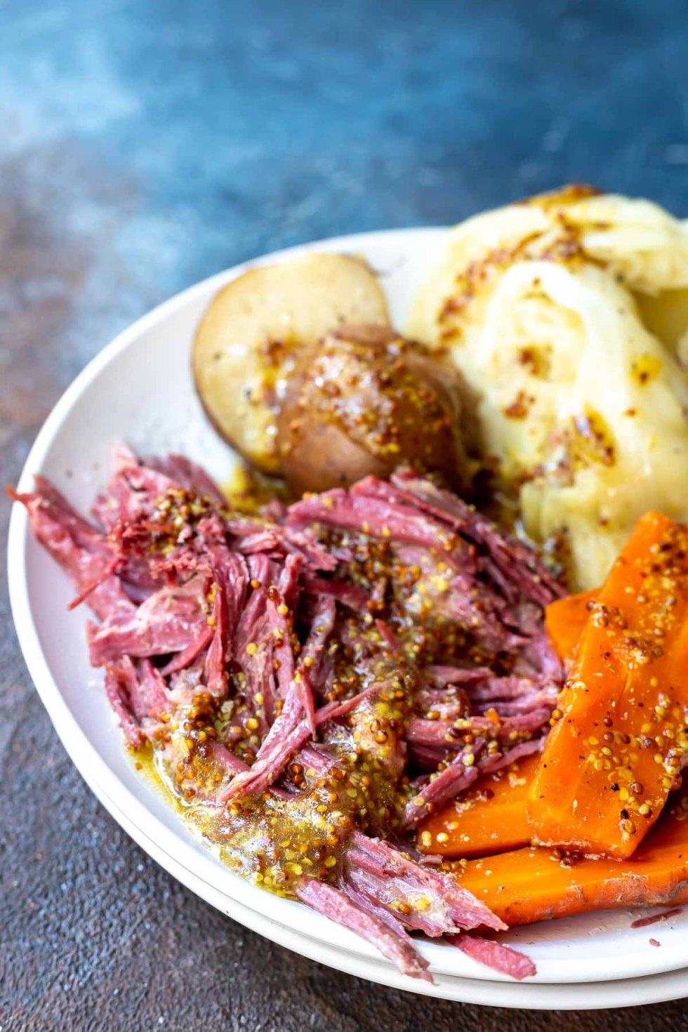 white plate with crockpot corned beef cabbage, carrots and potatoes