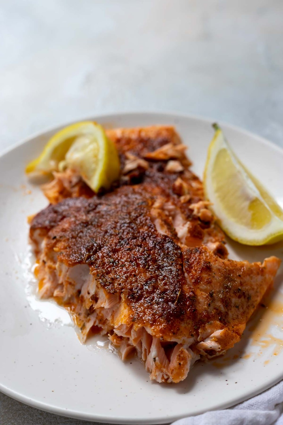 piece of blackened salmon served on a white plate with lemon wedges
