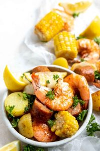 sheet pan shrimp boil shrimp, corn, potatoes, sausage and lemons in a white dish