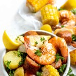 sheet pan shrimp boil shrimp, corn, potatoes, sausage and lemons in a white dish