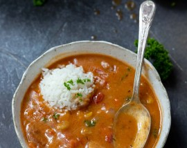 chicken and sausage gumbo in white bowl with spoon