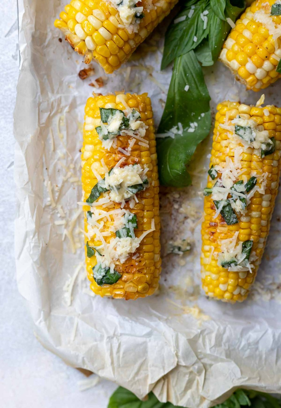 baked corn on the cob on white parchment paper with parmesan basil butter on top