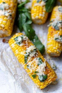 oven roasted corn on the cob topped with butter, parmesan cheese and fresh basil