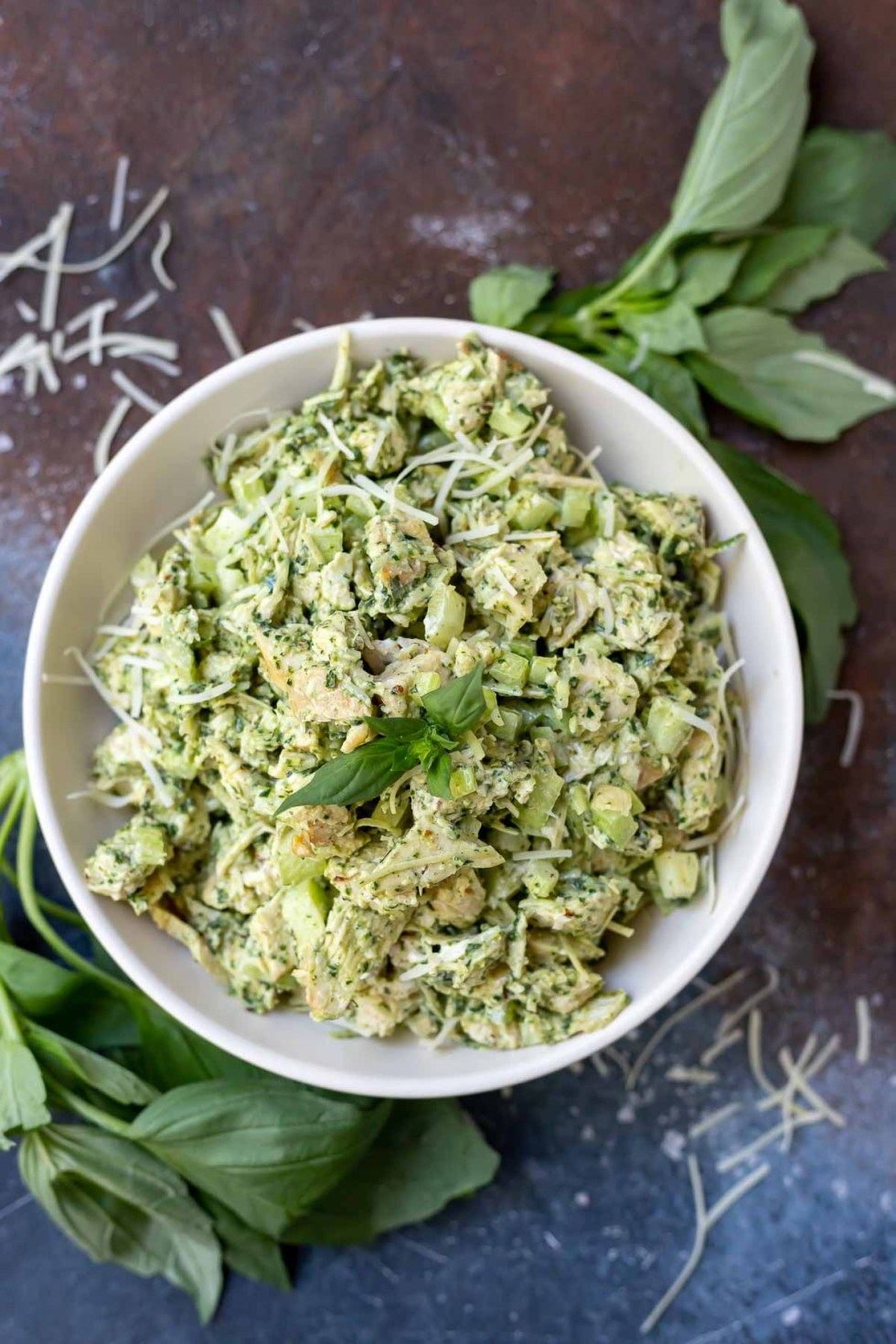 pesto chicken salad in white bowl surrounded by fresh basil