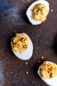 deviled eggs topped with chili flakes and chives