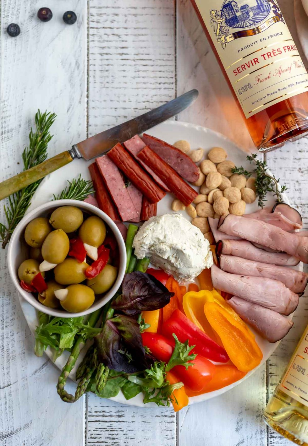 meat and cheese board with olives and sliced sweet peppers