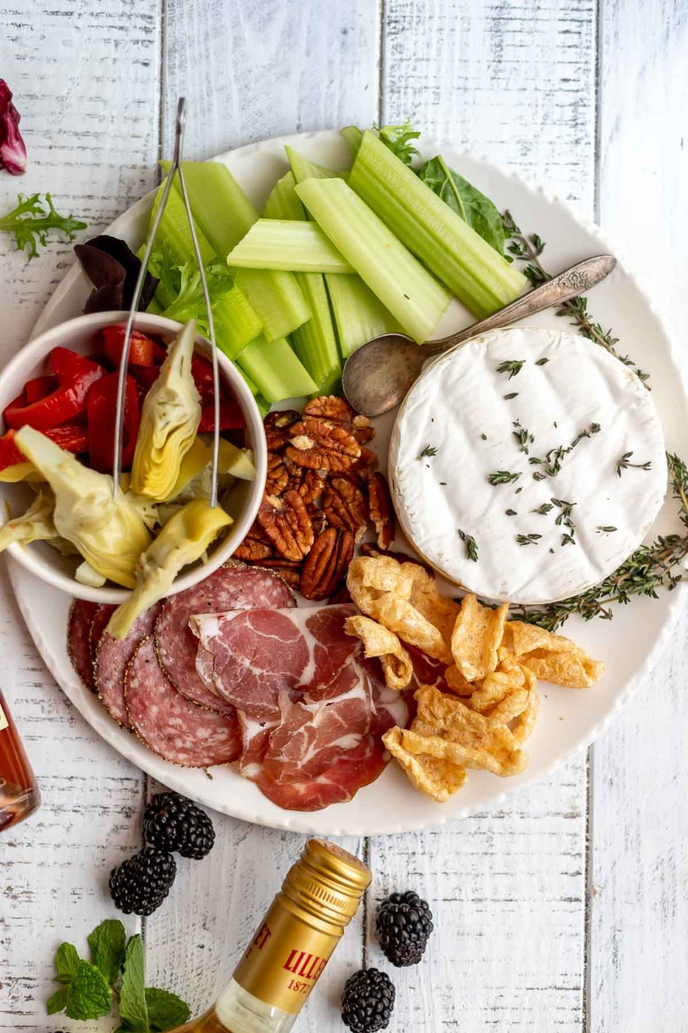 charcuterie board with brie, meat, pork rinds and artichoke hearts