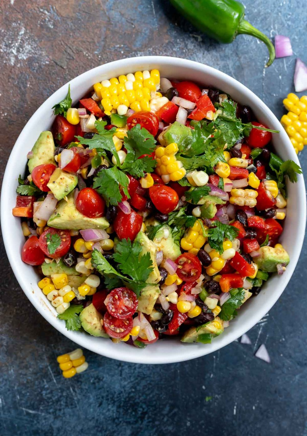 fresh corn salad topped with cilantro in white bowl
