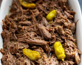 shredded beef pot roast in white serving dish