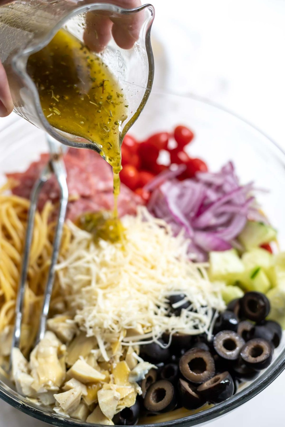 italian dressing being poured over spaghetti pasta salad