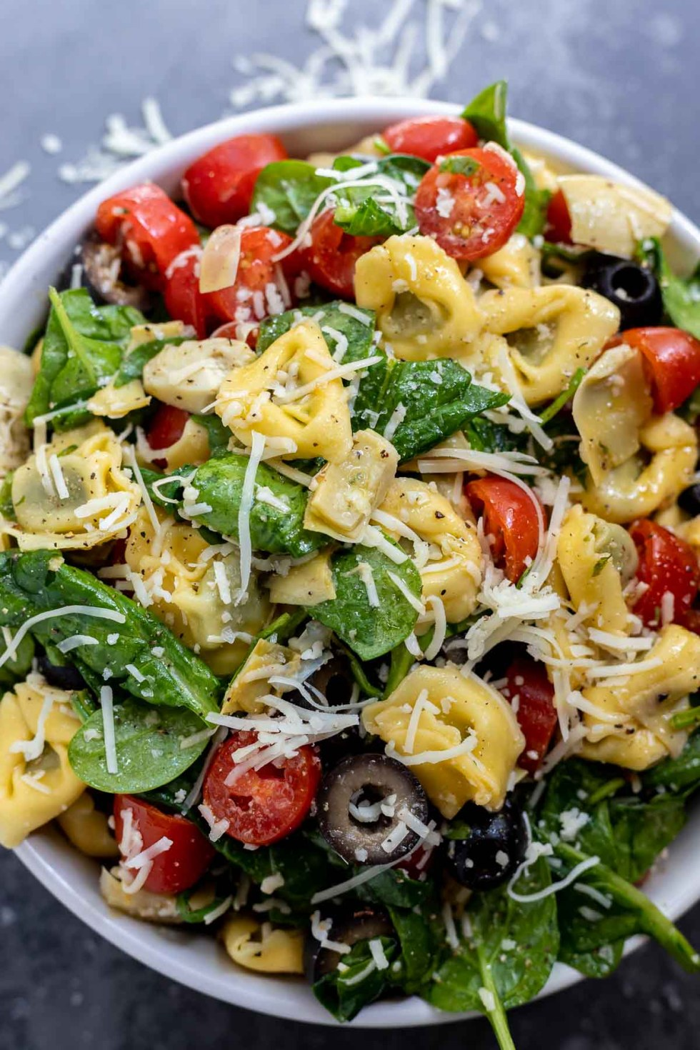tortellini salad with veggies and parmesan cheese in white bowl