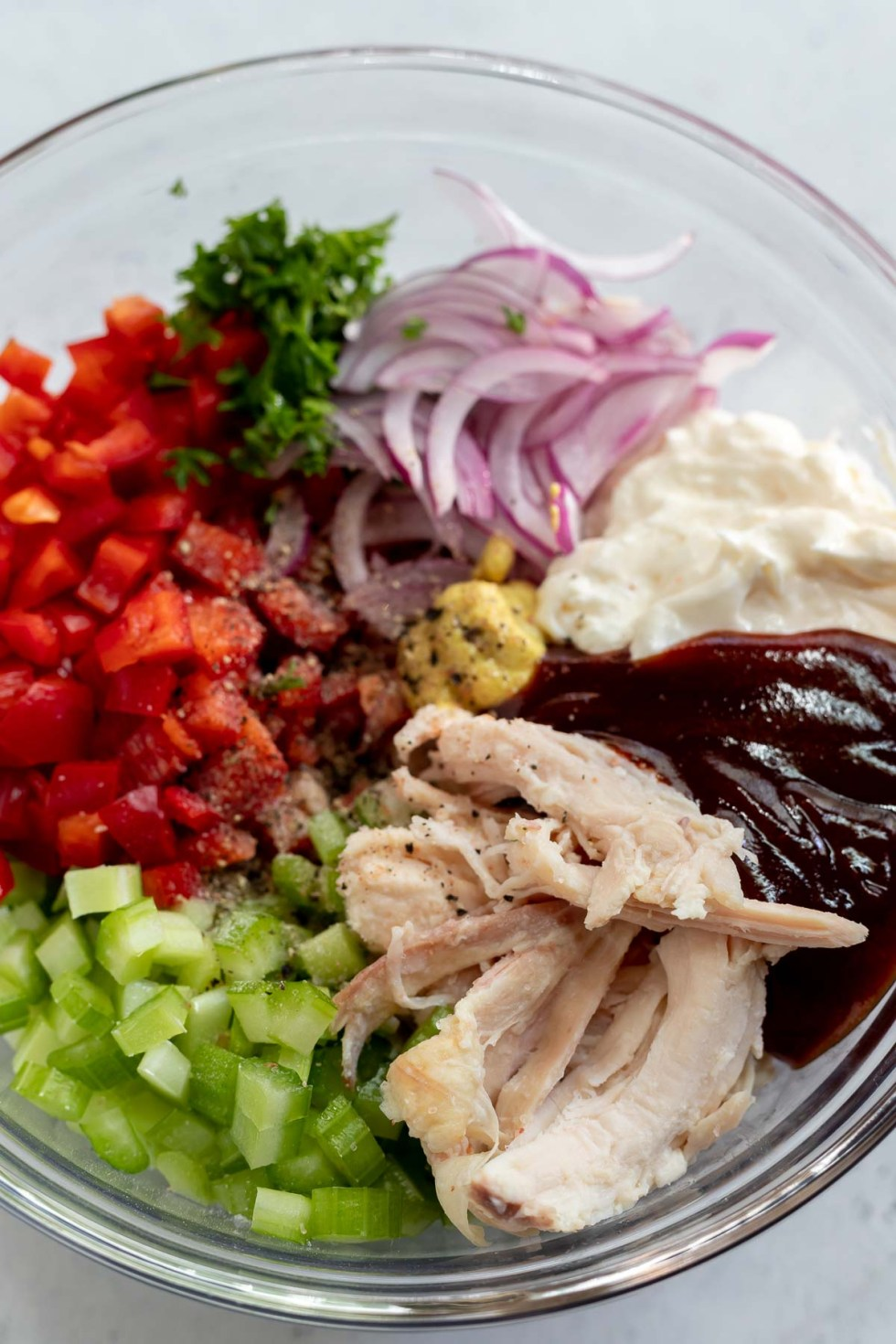 barbecue chicken salad ingredients in clear glass bowl